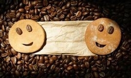 Due biscotti sorridenti sull'etichetta del pacchetto con i chicchi di caffè arrostiti Fotografia Stock