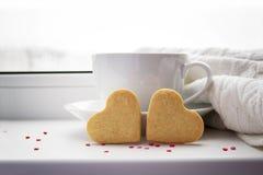 Due biscotti sotto forma di un cuore su un fondo con una tazza Fotografia Stock