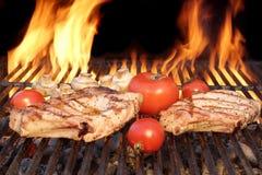 Due bistecche e verdure Carbone-grigliate sopra fiammeggiare la griglia del BBQ Fotografia Stock Libera da Diritti