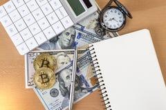 Due bitcoins, giornale, penna, calcolatore e orologi da tasca dorati Fotografia Stock