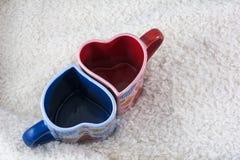 Due blu e tazze rosse nella forma di cuore Immagini Stock Libere da Diritti