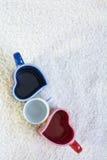 Due blu e tazze rosse nella forma di cuore e di piccolo quello bianco Immagini Stock Libere da Diritti