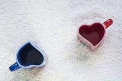 Due blu e tazze rosse nella forma di cuore a parte Immagini Stock