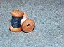 Due bobine di cucito con i fili variopinti si trovano sul fondo del denim Fotografia Stock