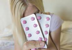 Due bolle delle compresse rosa, pillole si chiudono su a disposizione della donna bionda vaga, sedendosi sul letto immagini stock libere da diritti