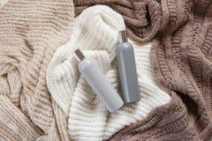 Due bottiglie del detersivo di lavanderia liquido in bianco sul fondo tricottato colorato di struttura Vista superiore Fotografia Stock