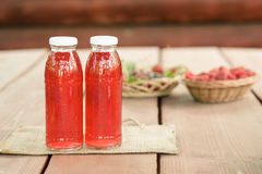 Due bottiglie del freddo hanno stufato la frutta dalle bacche assortite Immagini Stock