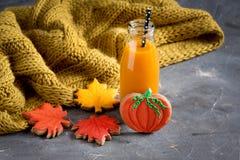 Due bottiglie del succo della zucca con l'alimento orizzontale di Halloween della foto delle paglie nere ed il concetto dei dolci Immagini Stock Libere da Diritti