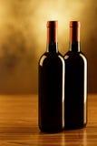 Due bottiglie del vino rosso sulla tavola di legno e sul fondo dorato Fotografie Stock