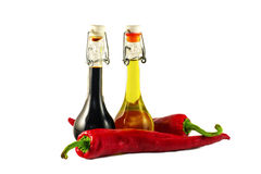 Due bottiglie dell'aceto di vino, dell'olio d'oliva e del pe freddo rovente due Fotografia Stock Libera da Diritti