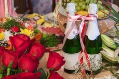 Due bottiglie di champagne legate con un nastro in mezzo ai mazzi dei fiori, indicando una festa nuziale o l'altro festivo fotografie stock