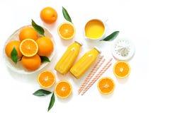 Due bottiglie di vetro di succo d'arancia, di paglie fresche e delle arance isolati sulla vista superiore del fondo bianco immagini stock libere da diritti