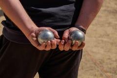 Due boules del petanque nelle mani di un giocatore fotografie stock libere da diritti