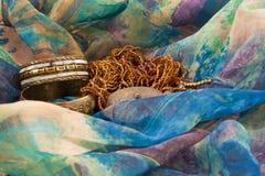 Due braccialetti e una collana su una seta multicolore Fotografia Stock