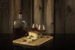 Due Brandy Snifters, bordo del formaggio e bottiglia di brandy immagini stock libere da diritti