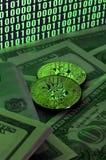 Due bugie dei bitcoins su un mucchio delle banconote in dollari sui precedenti di un monitor che descrive un codice binario degli Immagine Stock Libera da Diritti