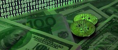 Due bugie dei bitcoins su un mucchio delle banconote in dollari sui precedenti di un monitor che descrive un codice binario degli Immagini Stock Libere da Diritti