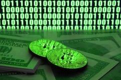 Due bugie dei bitcoins su un mucchio delle banconote in dollari sui precedenti di un monitor che descrive un codice binario degli Fotografie Stock