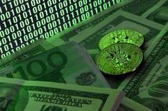 Due bugie dei bitcoins su un mucchio delle banconote in dollari sui precedenti di un monitor che descrive un codice binario degli Fotografia Stock