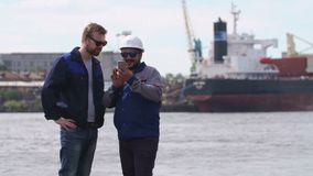 Due buoni amici, lavoratori di porto e colleages esaminano lo smartphone e dicono arrivederci nel porto del carico di trasporto video d archivio