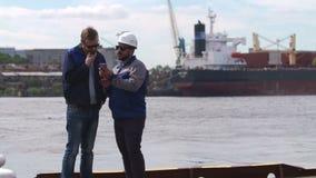 Due buoni amici, lavoratori di porto e colleages esaminano lo smartphone nel porto del carico di trasporto stock footage