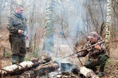 Due cacciatori sopra il fuoco di accampamento Fotografie Stock