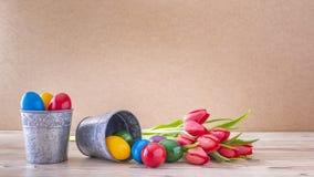 Due calici d'argento con le uova di Pasqua variopinte ed i tulipani rossi immagine stock