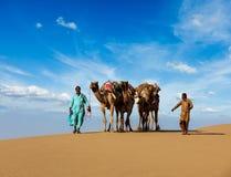 Due cameleers (driver del cammello) con i cammelli in dune del deser di Thar fotografie stock