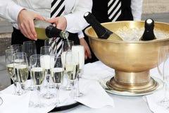 Due camerieri riempiono i vetri di champagne Fotografie Stock Libere da Diritti