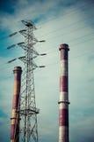 Due camini industriali ed e un pilone elettrico ad alta tensione Fotografia Stock