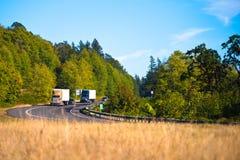 Due camion potenti dei semi sulla strada principale di bobina Fotografia Stock