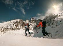 Due camminatori dello sci delle donne vanno su sulla cima della montagna immagini stock