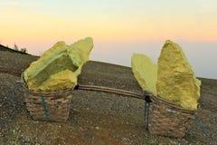 Due canestri con i grandi pezzi dello zolfo pesante dal vulcano di Ijen Fotografia Stock