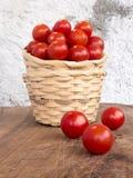 Due canestri di vimini impilati con una manciata di pomodori di pachino Fotografia Stock Libera da Diritti