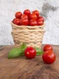Due canestri di vimini impilati con una manciata di pomodori di pachino Fotografia Stock