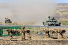 Due carri armati moderni russi T-90 stanno muovendo lungo la terra di addestramento militare Fotografia Stock