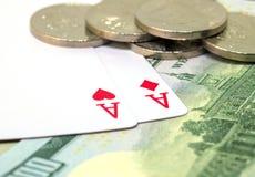 Due carte da gioco, banconote e monete Mano di mazza di conquista Cuori ed asso dei diamanti sulla tavola Immagini Stock