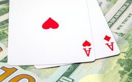 Due carte da gioco sul fondo dei soldi Mano di mazza di conquista Cuori ed asso dei diamanti sulla tavola Fotografia Stock Libera da Diritti