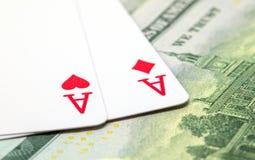 Due carte da gioco sul fondo del dollaro Mano di mazza di conquista Cuori ed asso dei diamanti sulla tavola Fotografia Stock