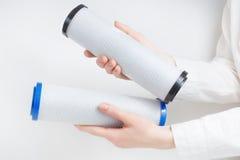 Due cartucce di filtro dall'acqua in mani umane Immagine Stock