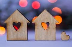Due case di legno con il foro sotto forma di cuore con poco hea Fotografie Stock