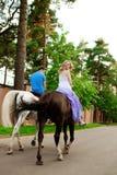 Due cavalieri a cavallo al tramonto sulla spiaggia Hors di giro degli amanti Fotografia Stock Libera da Diritti