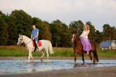 Due cavalieri a cavallo al tramonto sulla spiaggia Hors di giro degli amanti immagine stock libera da diritti