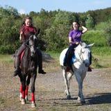 Due cavalli di guida delle ragazze Fotografia Stock Libera da Diritti