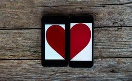Due cellulari con il mezzo simbolo del cuore Immagine Stock