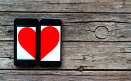 Due cellulari con il mezzo simbolo del cuore Immagine Stock Libera da Diritti
