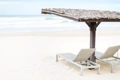 Due chaise longue vuote sotto la tettoia sulla spiaggia. Immagine Stock