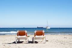 Due chaise-lounge sulla spiaggia con una vista degli yacht e delle navi Immagini Stock