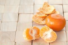 Due che rinfrescano, mandarini succosi freschi dall'albero su una stuoia di posto contemporanea e moderna di legno, il raccolto d Immagini Stock