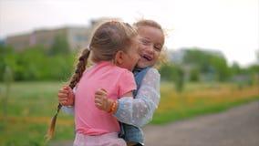 Due che sorridono, neonate ricce e sveglie delle sorelle per abbracciarsi strettamente Infanzia felice, emozioni positive, sensib video d archivio